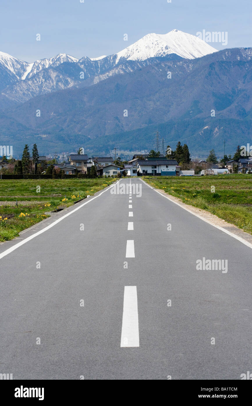 Empty Road Leading To Houses in Northern Alps, Hokkaido Stock Photo