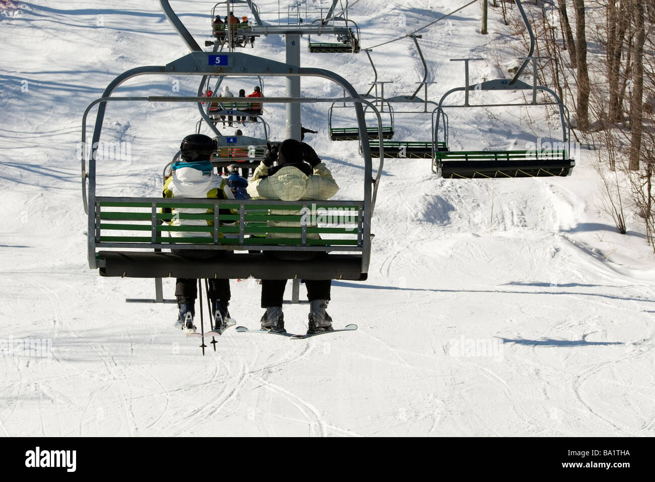 Two people on chairlift ready to go skiing - Stock Image