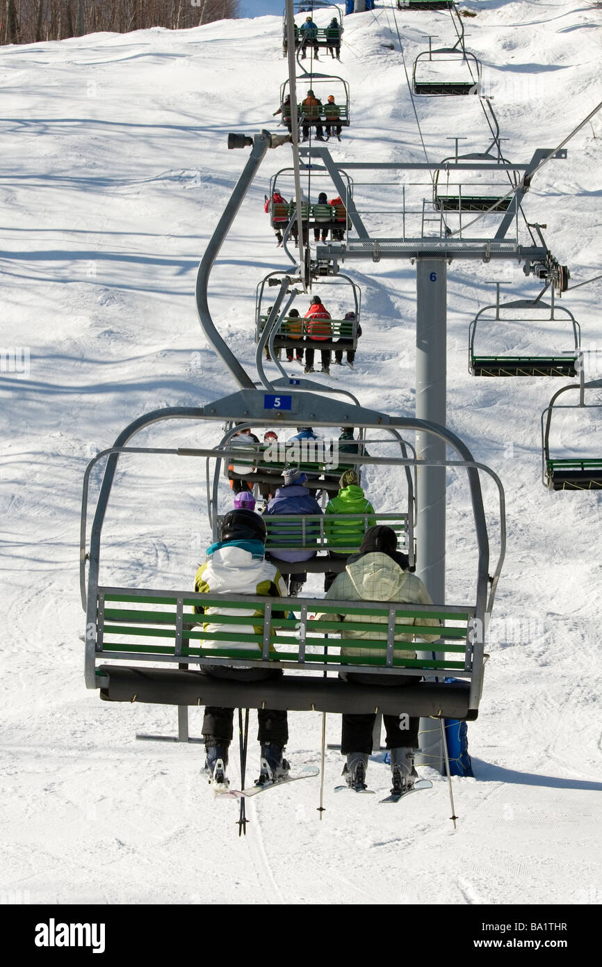 Chairlift full of people on there way up the mountain - Stock Image