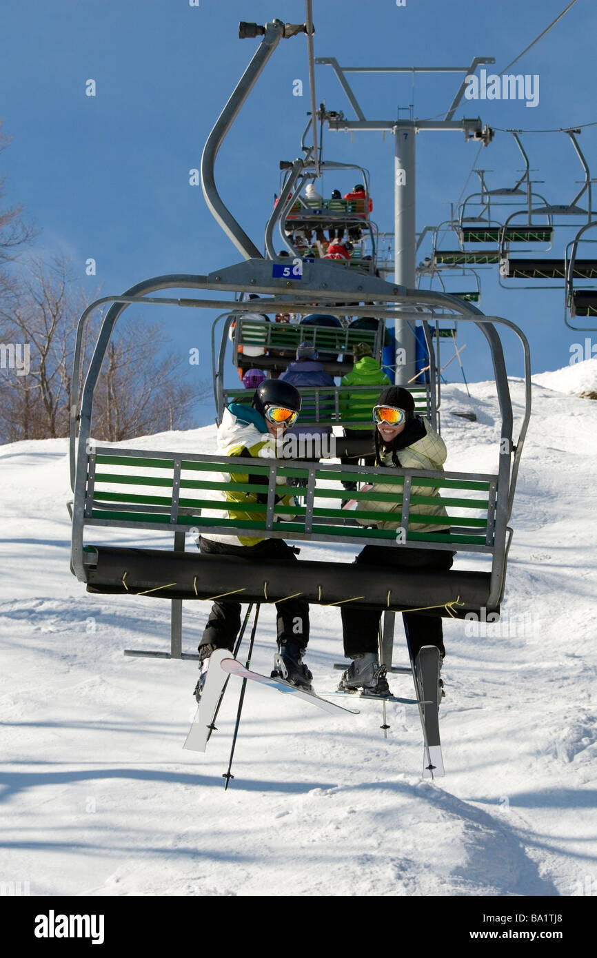 Two young girls on chairlift going up hill - Stock Image