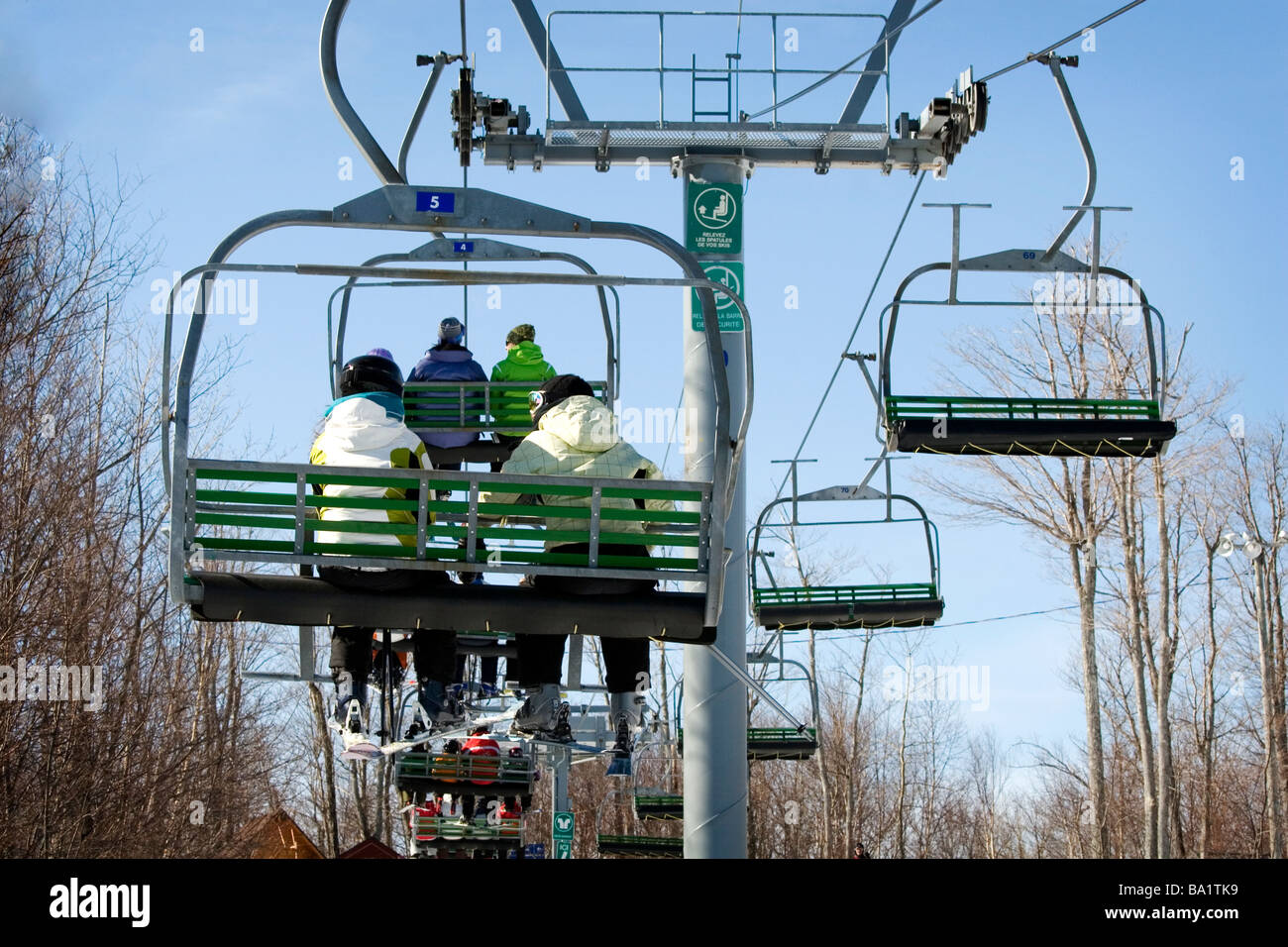 People on chairlift on there way up the mountain - Stock Image
