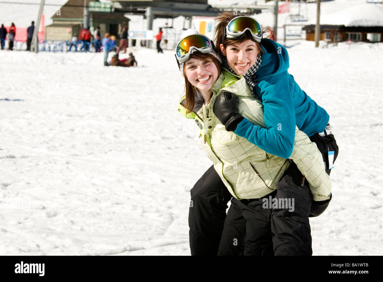 Two sisters in ski suits happy to be outside on a nice day during winter - Stock Image