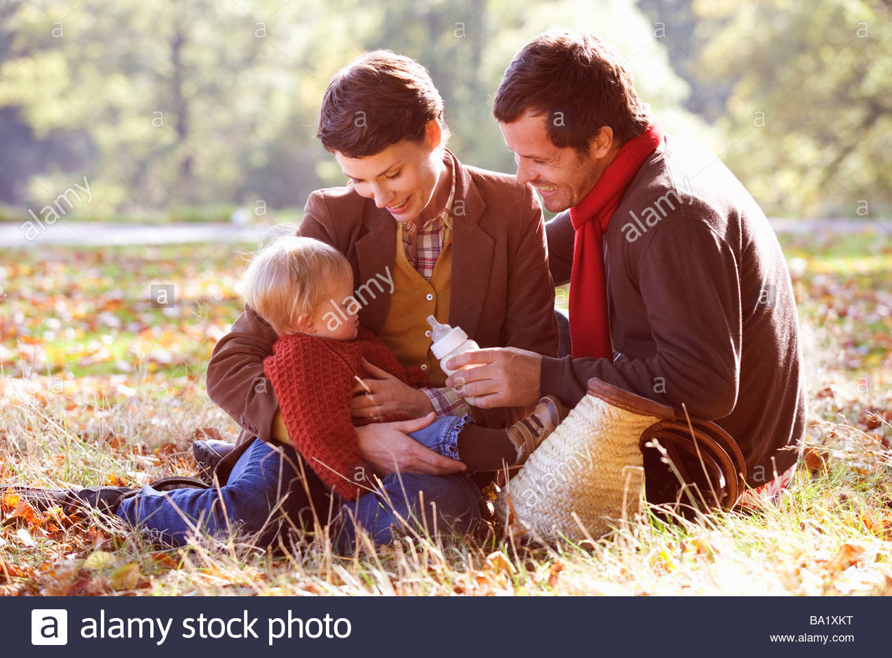 A young family sitting on the grass, father feeding the baby - Stock Image