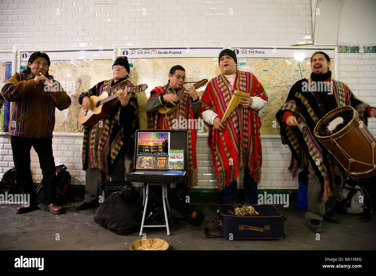 A customary scene in cosmopolitan Paris, a Peruvian pipe band perform to the rushing public in a busy underground - Stock Image