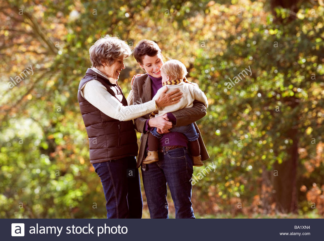 Mother and daughter smiling at baby - Stock Image