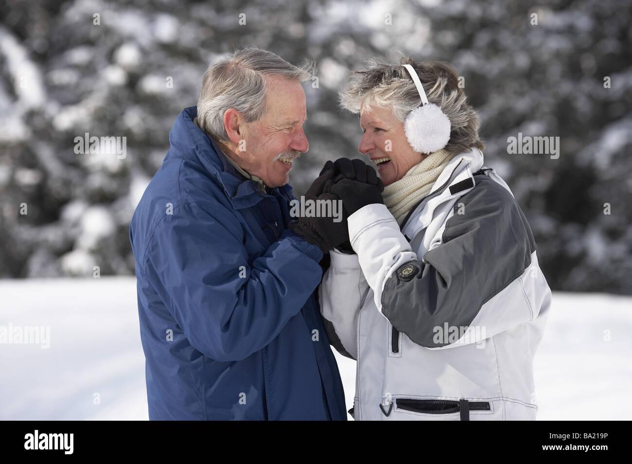 Senior-pairs winter-clothing gaze-contact laugh semi-portrait winters series people 60-70 years pair seniors winter - Stock Image