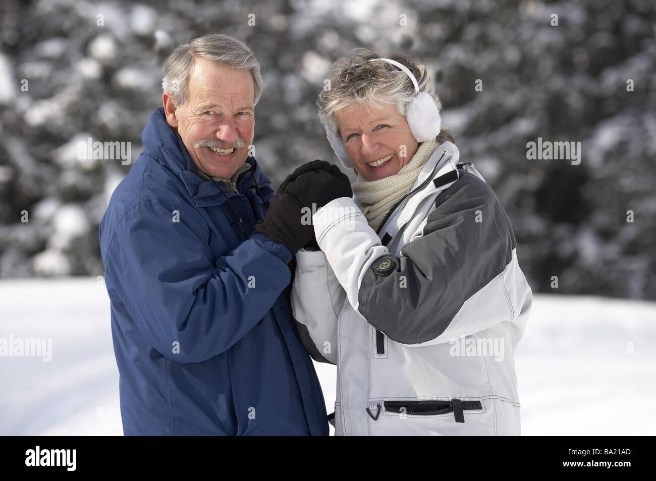 Senior-pairs winter-clothing semi-portrait laugh winters series people 60-70 years pair seniors winter-jackets gloves - Stock Image