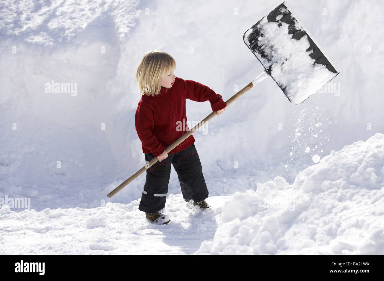 Give birth winter-clothing snow-shovels 4 years child blond ski-pants snow-shovel shovel holds shovels snow-evacuates - Stock Image