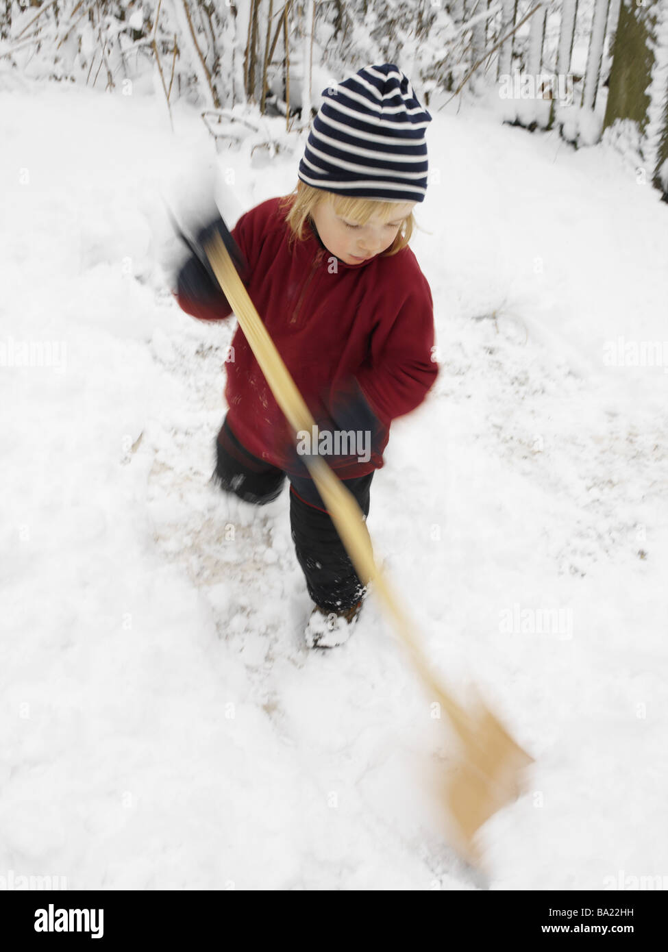 Give birth winter-clothing snow-shovels 4 years child blond ski-pants sweaters cap snow-shovel shovel shovels snow - Stock Image