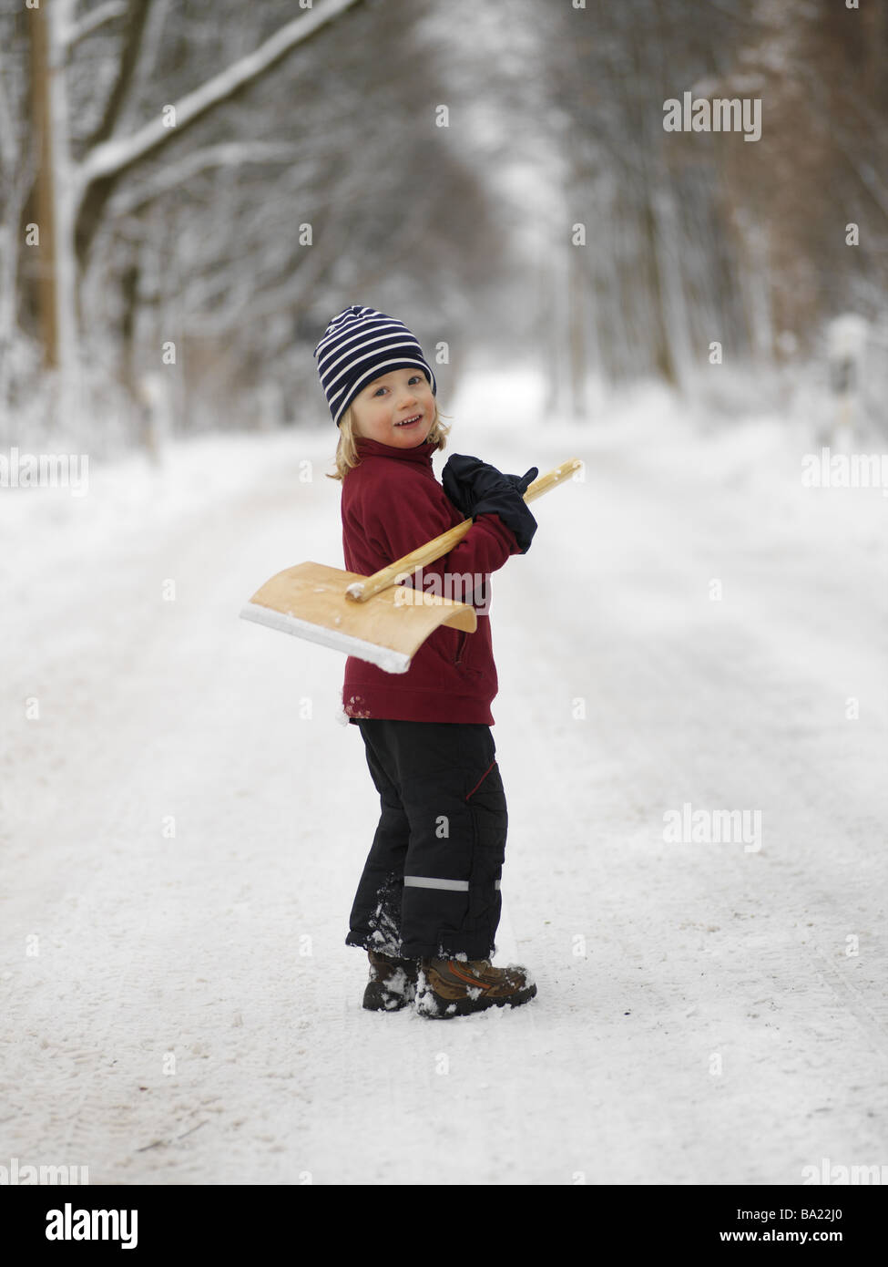 Forest path boy winter-clothing snow-shovel carries cheerfully 4 years child blond ski-pants sweaters cap wood-shovel - Stock Image