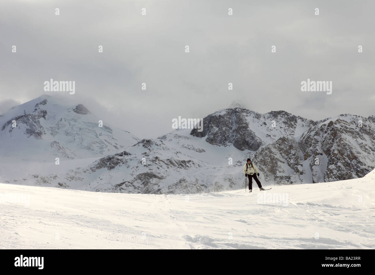 Lone skier in the midst of a break in a snow storm in the ski resort of Tignes Le Lac, Espace Killy, France - Stock Image