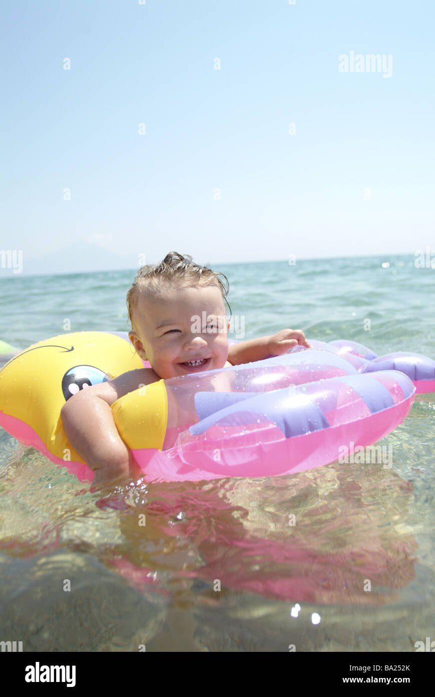 Girls smiles swimming-ring pink sea swims portrait people child-portrait child toddler 1-2 years childhood cheerfully - Stock Image