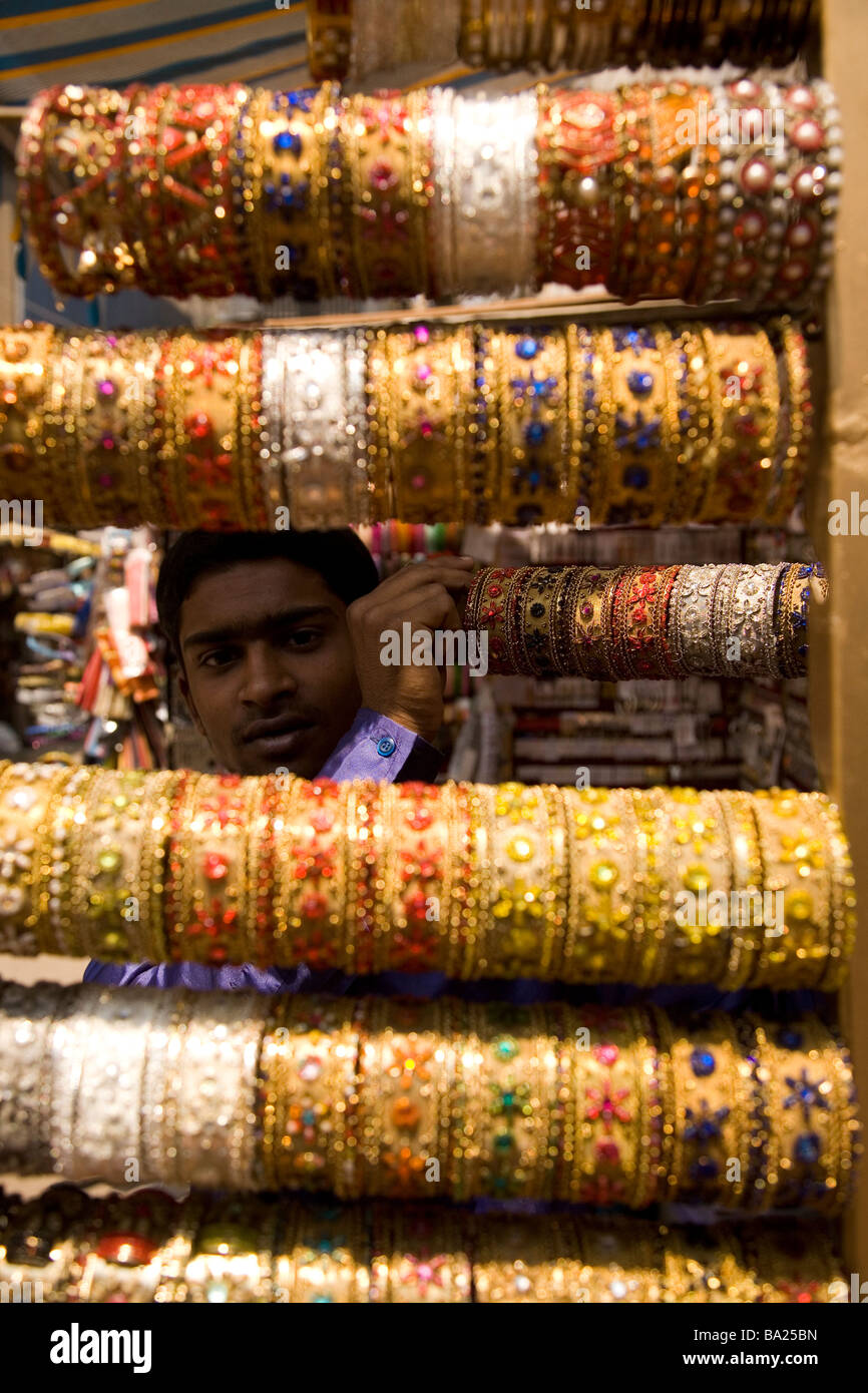 A young man holds up a set of bangles at a shop in Commercial Street in Bangalore, India. - Stock Image