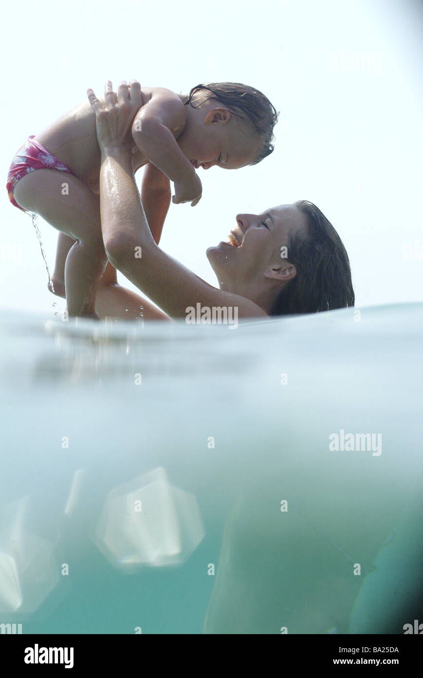 Mother daughter sea holds swims at the side broached fuzziness series people woman young 20-30 years long-haired - Stock Image