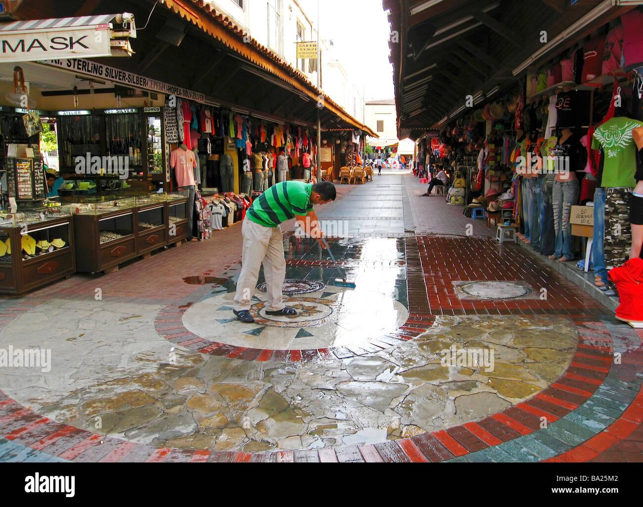 Man cleaning street bazaar in Alanya Turkey - Stock Image