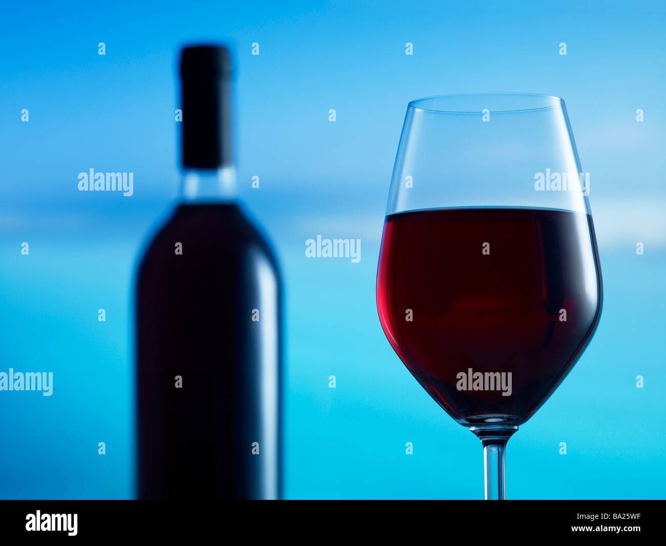 Glass of red wine with bottle in background 39MP capture - Stock Image
