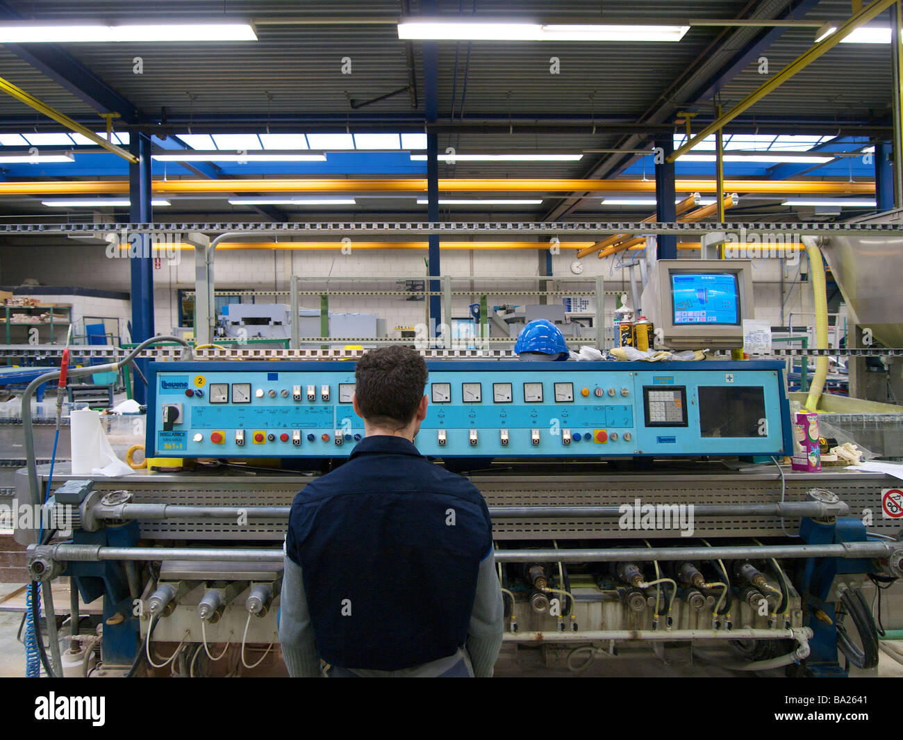 Man at control panel of industrial machine that is used for making nice edges on glass plates - Stock Image