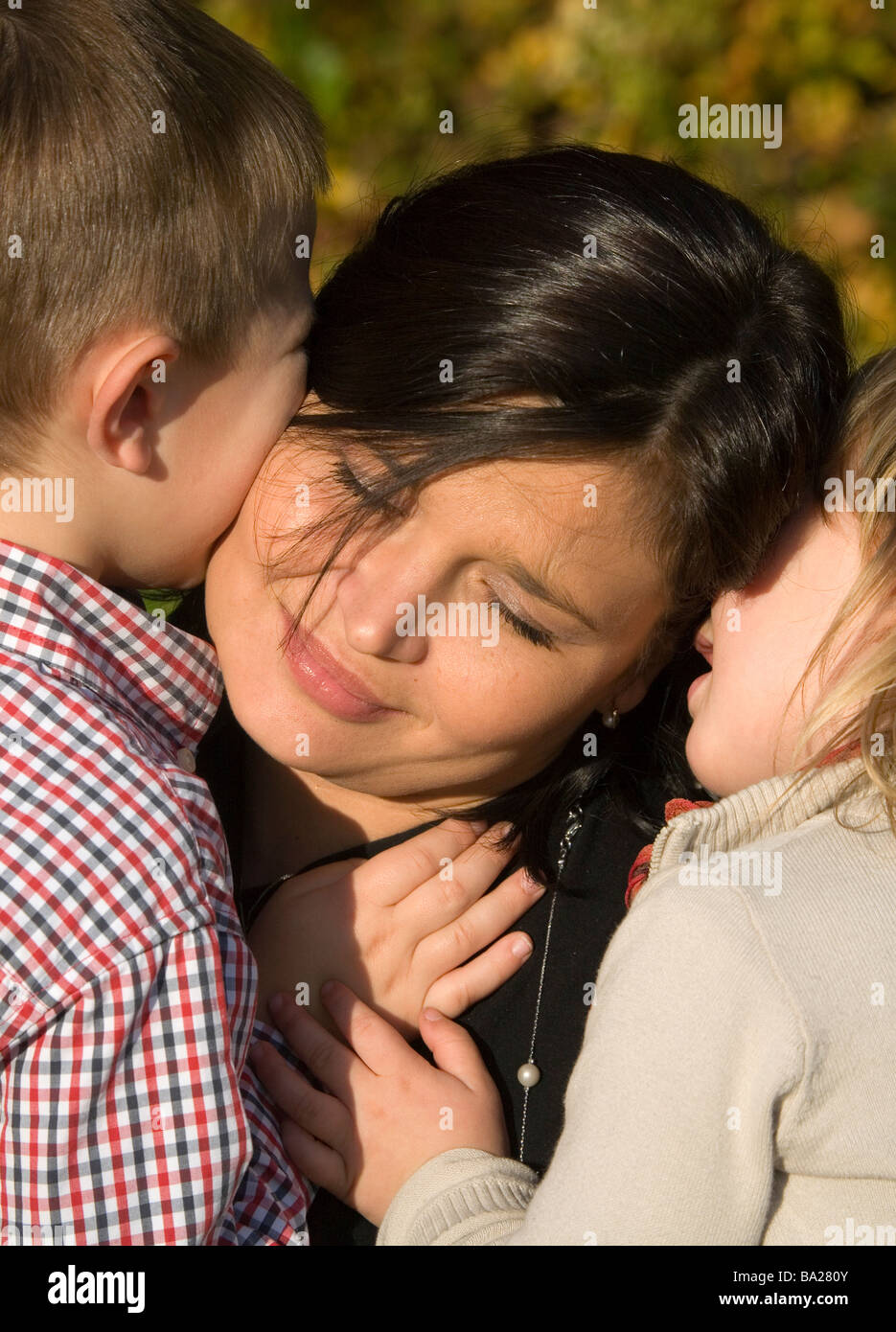 Mom with kid closes eyes with tender - Stock Image
