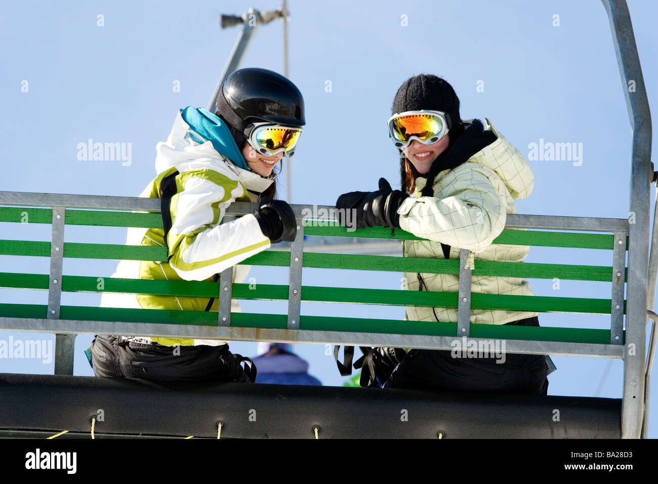 Two girls on chairlift ready to go skiing - Stock Image
