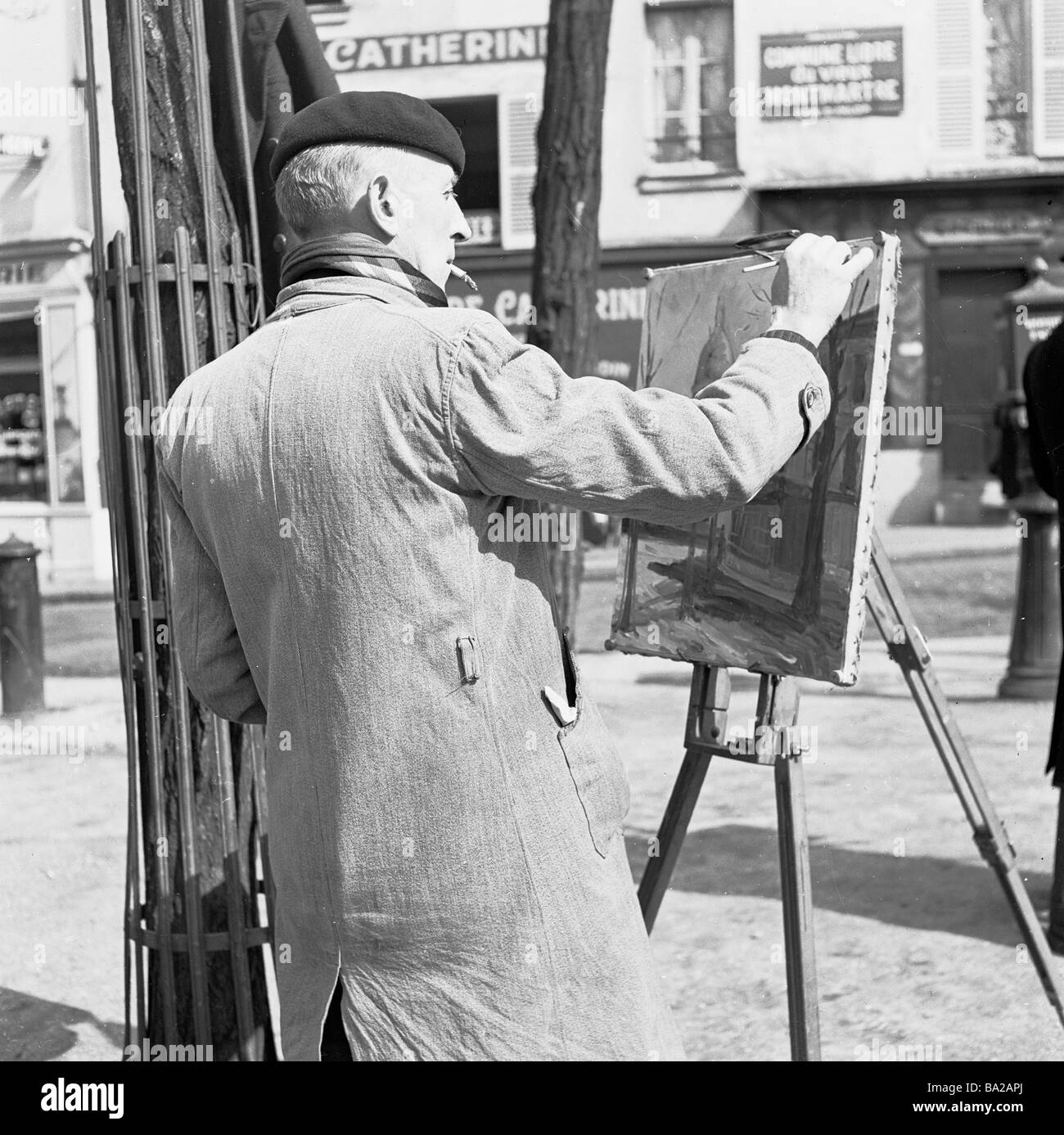 A french street artist wearing a berry,  raincoat and smoking, works on his canvas, Place du Tertre, Paris, France - Stock Image