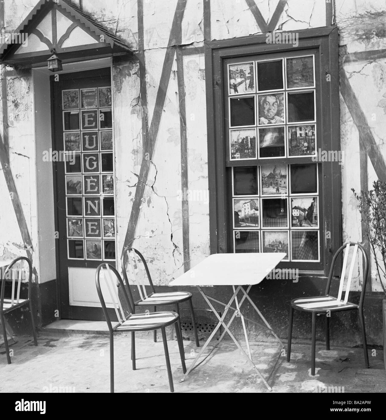 Exterior of Cafe Eugene in Place du Tertre Paris showing paintings in panes of window and door Paris France 1950 - Stock Image