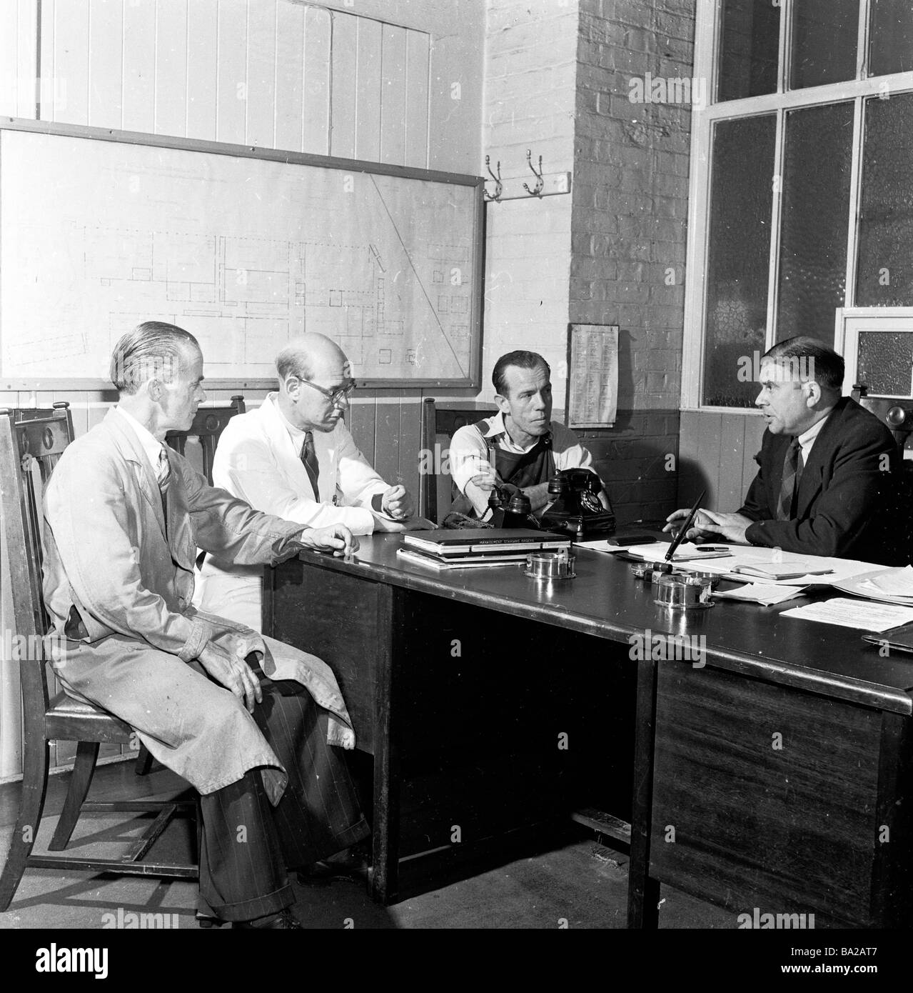 A meeting around the desk of the plant manager with foreman and workers' representative, Glacier Metal Company, - Stock Image