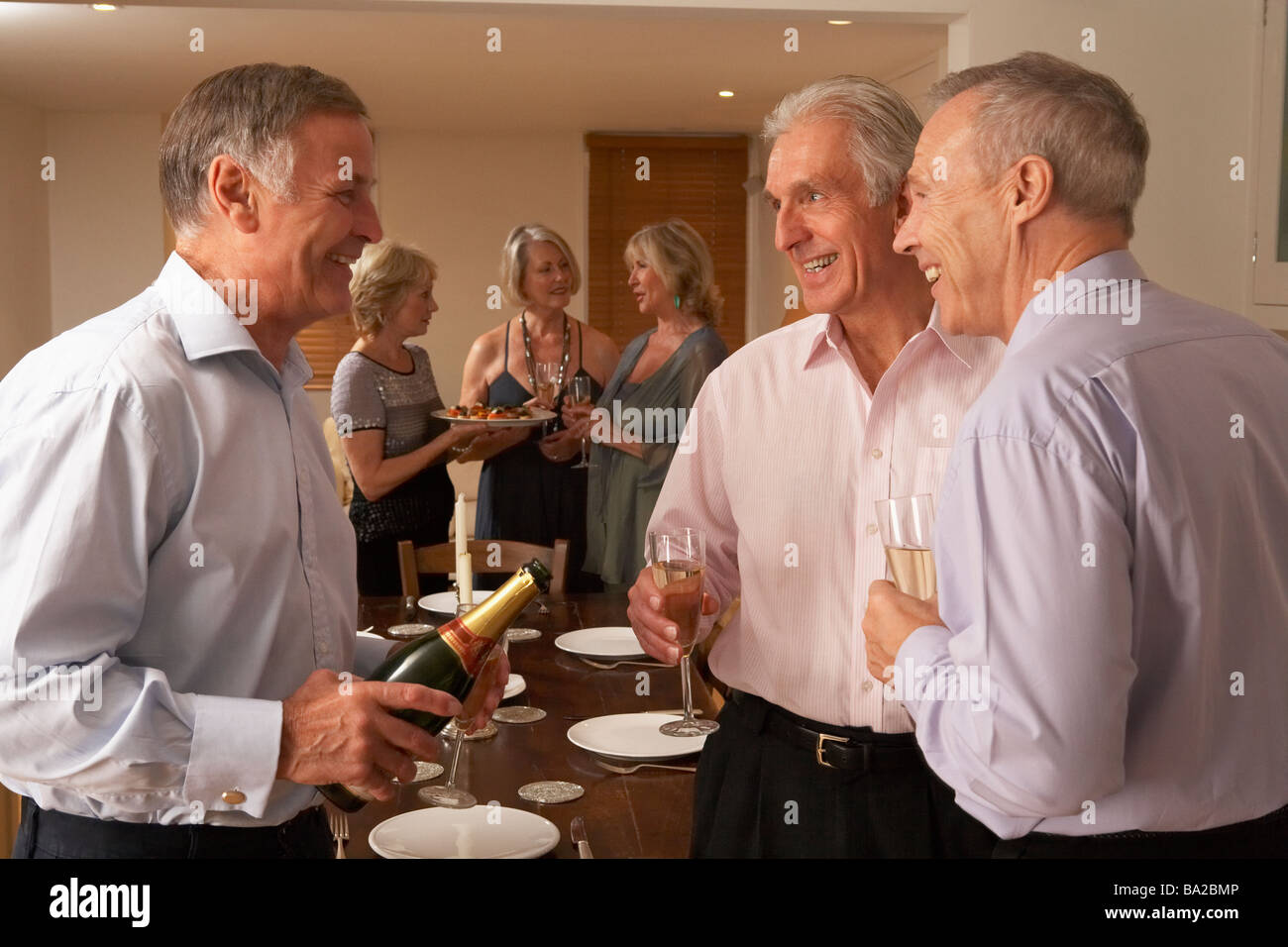 Man Serving Champagne To His Guests At A Dinner Party - Stock Image