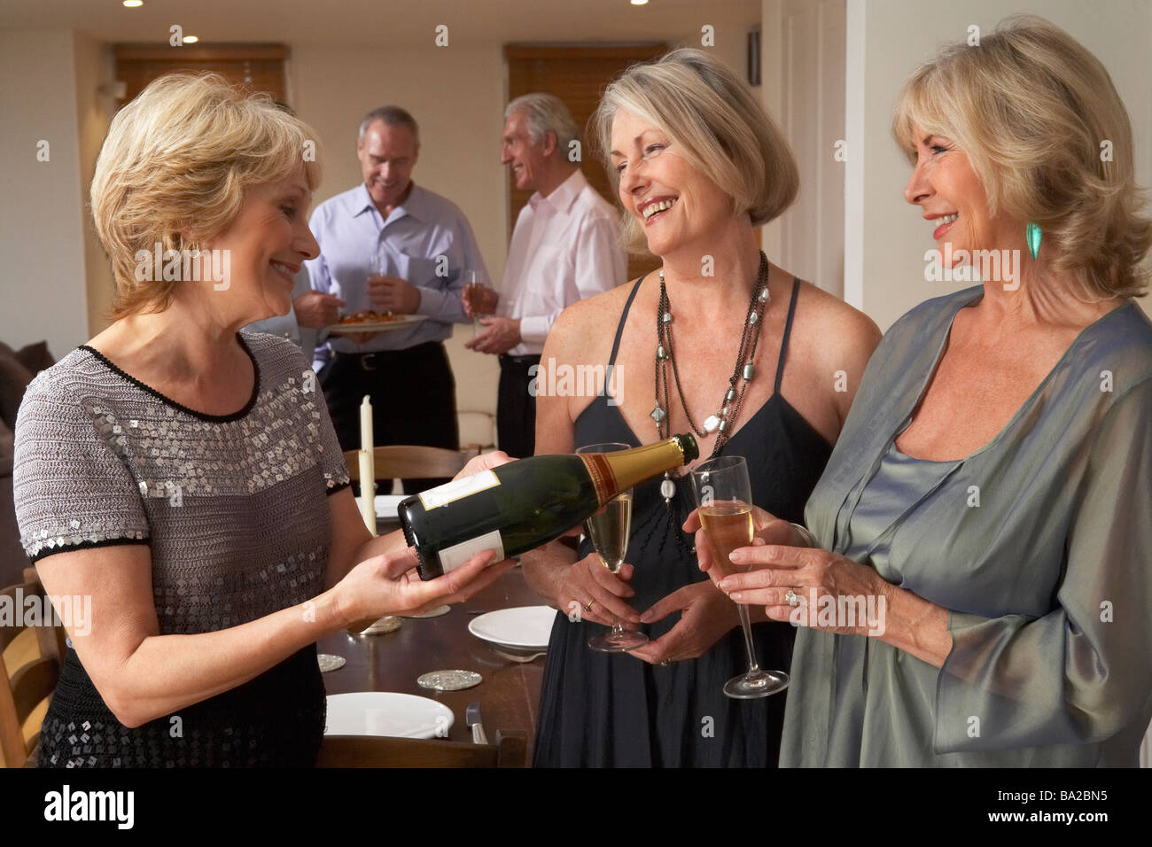 Woman Serving Champagne To Her Guests At A Dinner Party - Stock Image