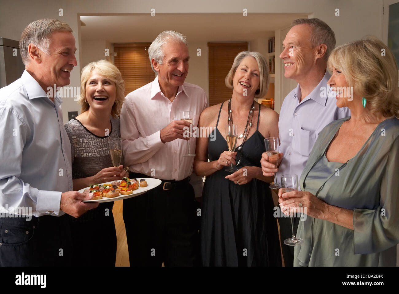 Man Serving Hors D'oeuvres To His Guests At A Dinner Party - Stock Image