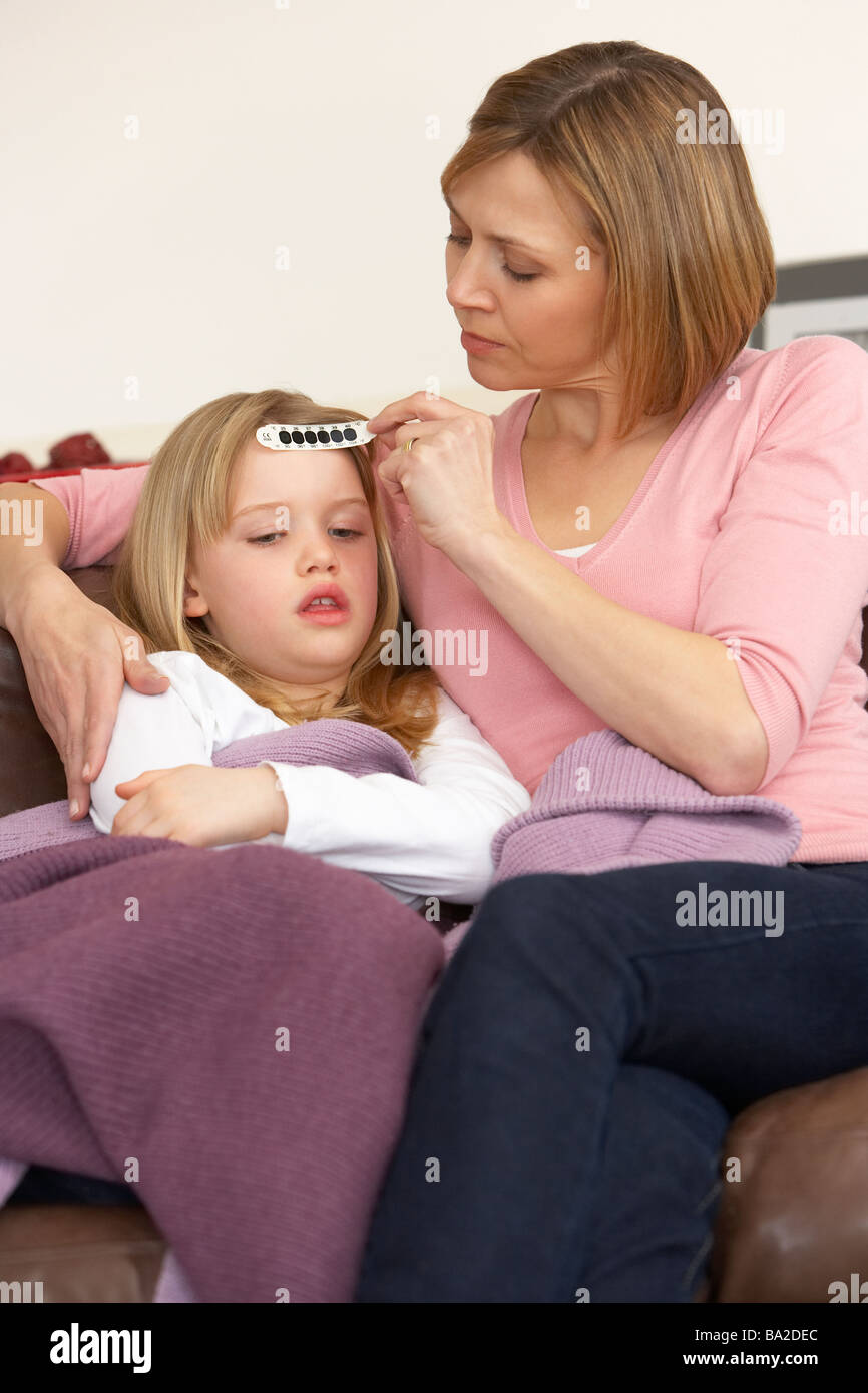 Mother Taking Temperature Of Sick Daughter - Stock Image