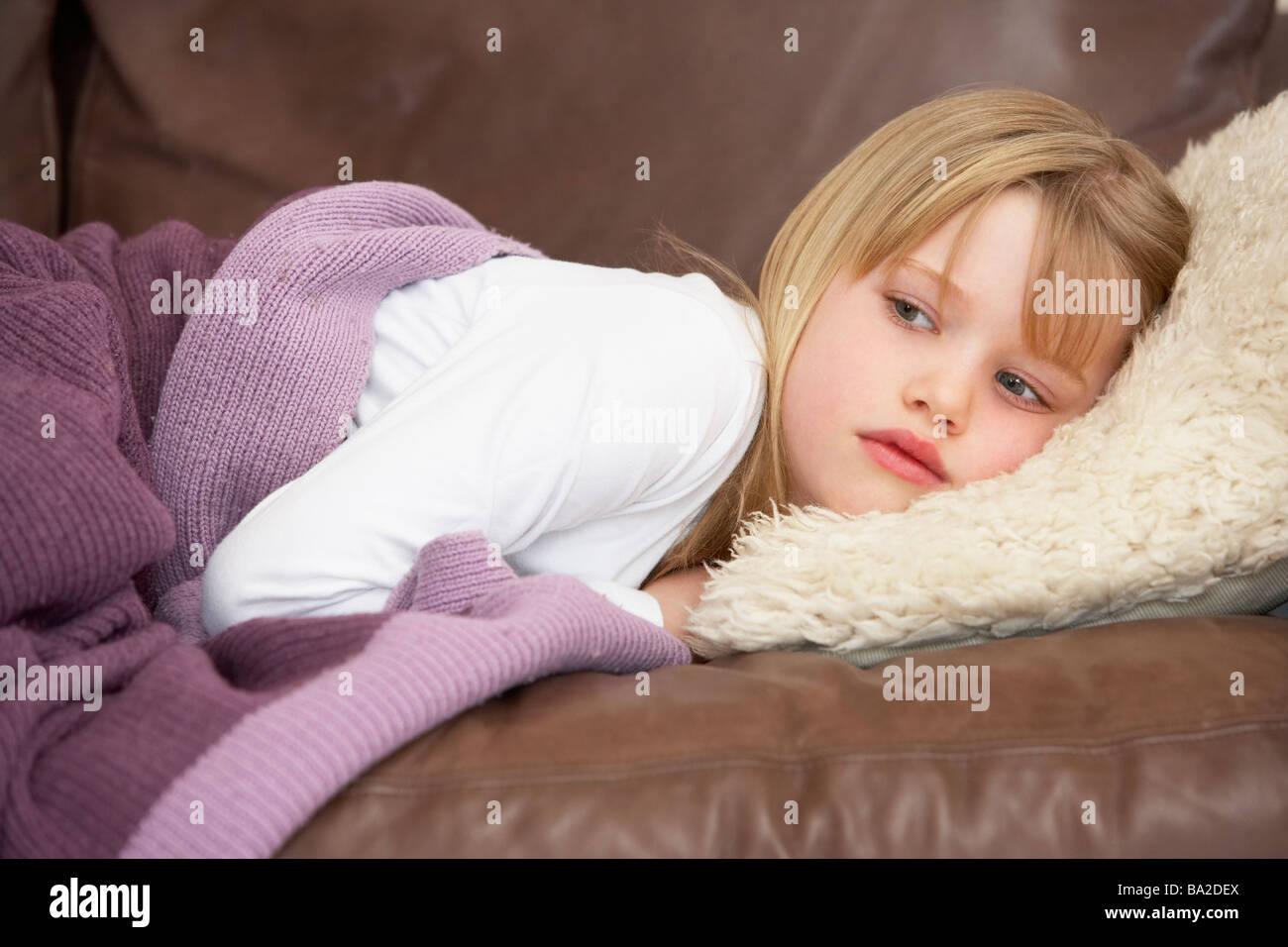 Young Girl Unwell Lying On Sofa - Stock Image