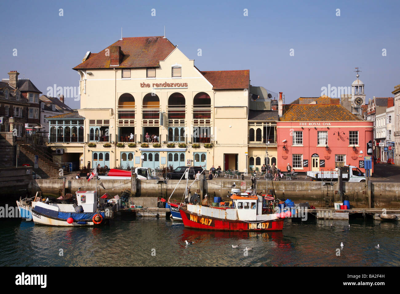 Fishing boats and harbourside pubs near the Town Bridge in the popular south coast resort of Weymouth - Stock Image