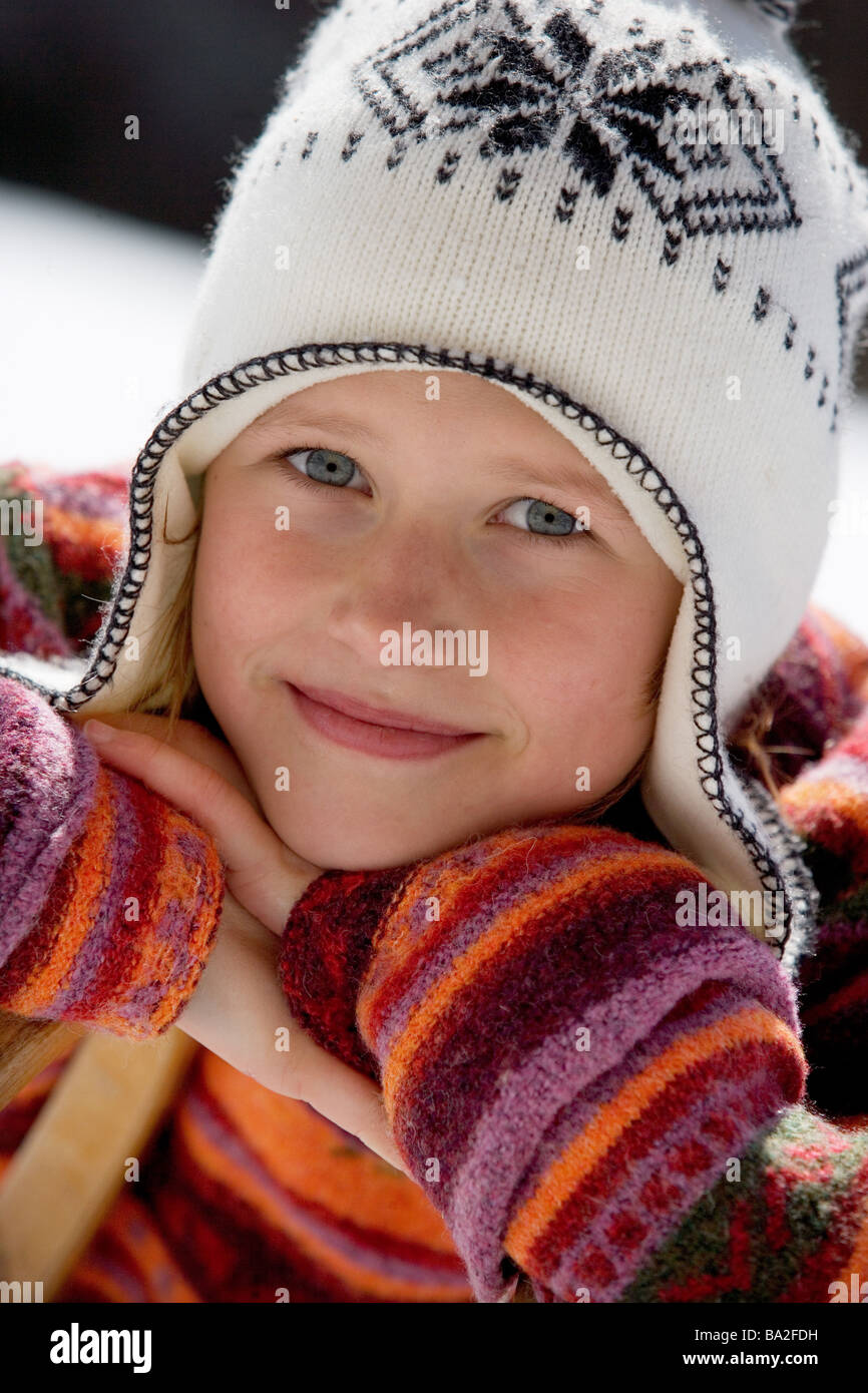 Girls cap winter-clothing smiles portrait winters leisure time child 10-15 years 13 years head rests wool-cap gaze - Stock Image