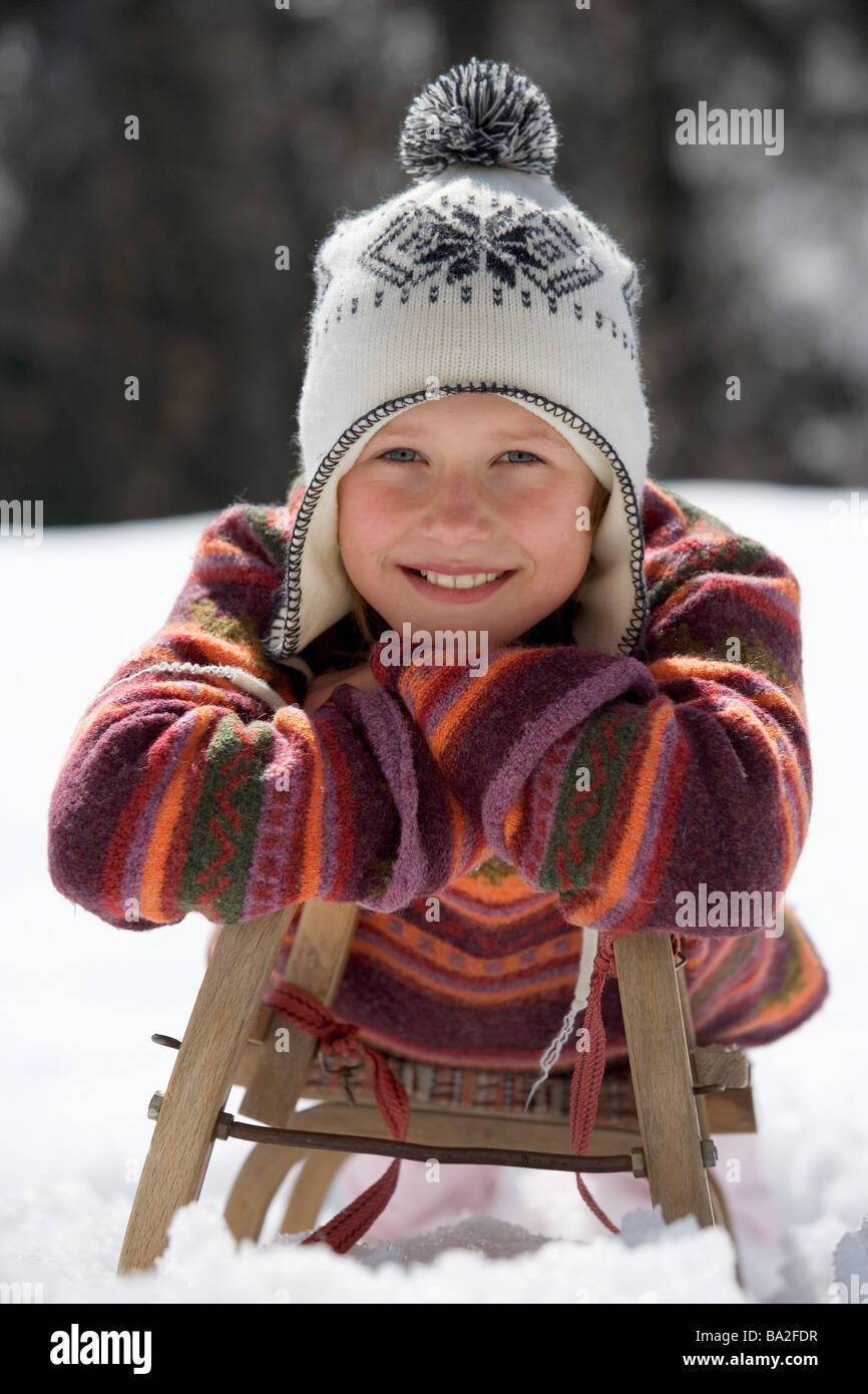 Girls cap winter-clothing smiles lies sleighs snow winters leisure time vacation winter-vacation vacation winter - Stock Image