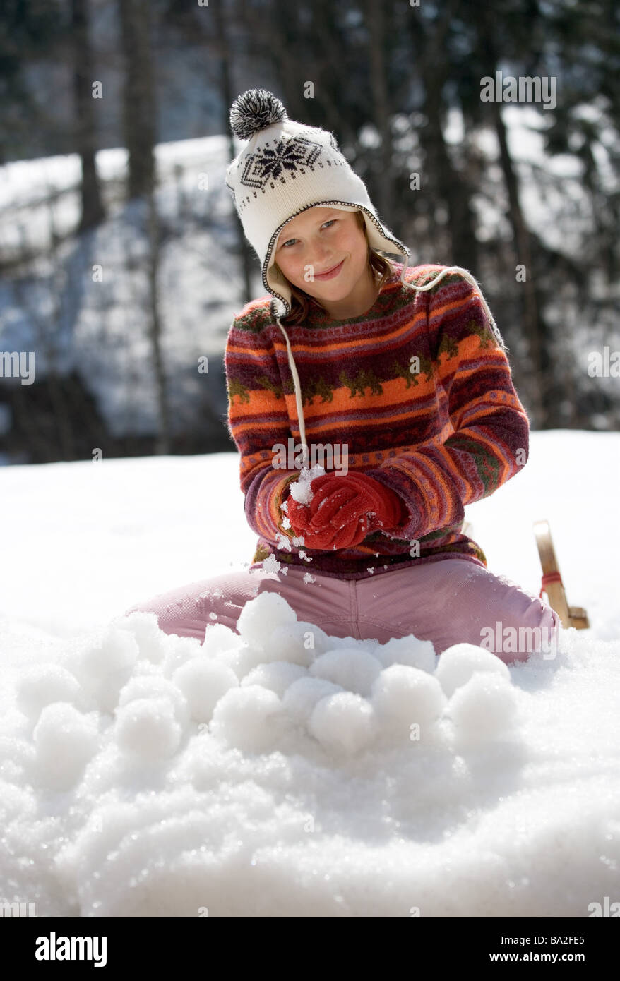 Girls cap winter-clothing smiles molds archly snowballs snow winters leisure time vacation winter-vacation vacation - Stock Image