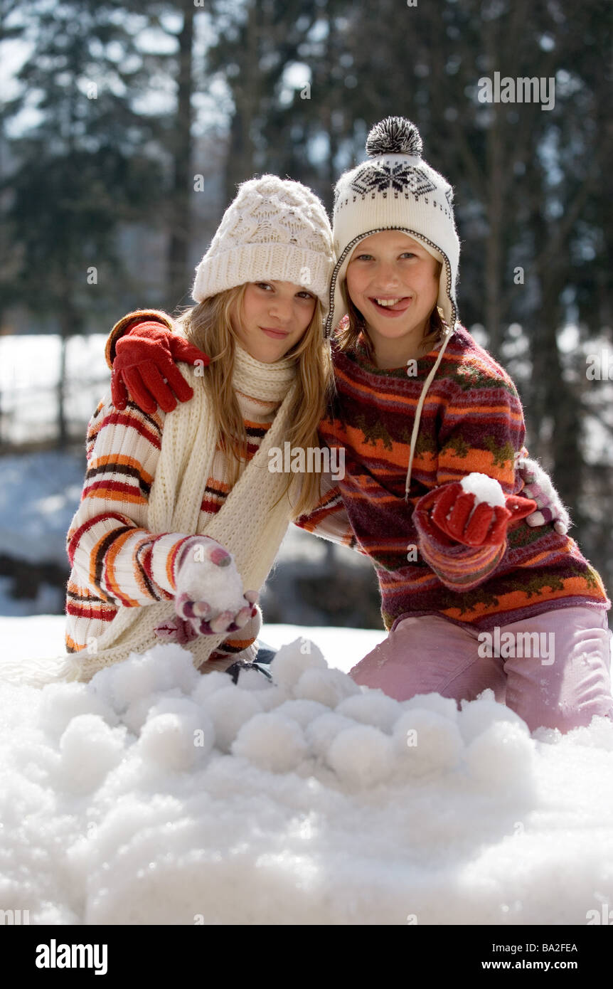Girls caps winter-clothing smiles presents archly snowballs snow winters leisure time vacation winter-vacation vacation - Stock Image