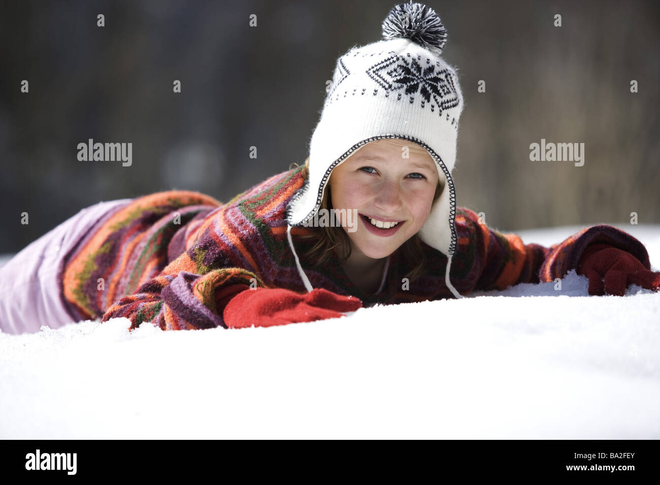 Girls cap winter-clothing smiles lies archly snow winters leisure time vacation winter-vacation vacation winter - Stock Image