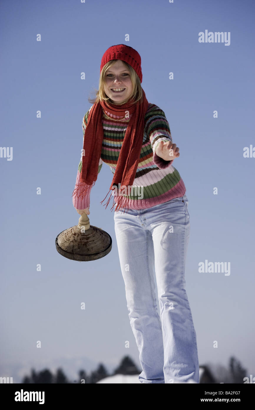 Woman young cap winter-clothing smiles ice-stick gesture winters leisure time vacation winter-vacation sport winter - Stock Image