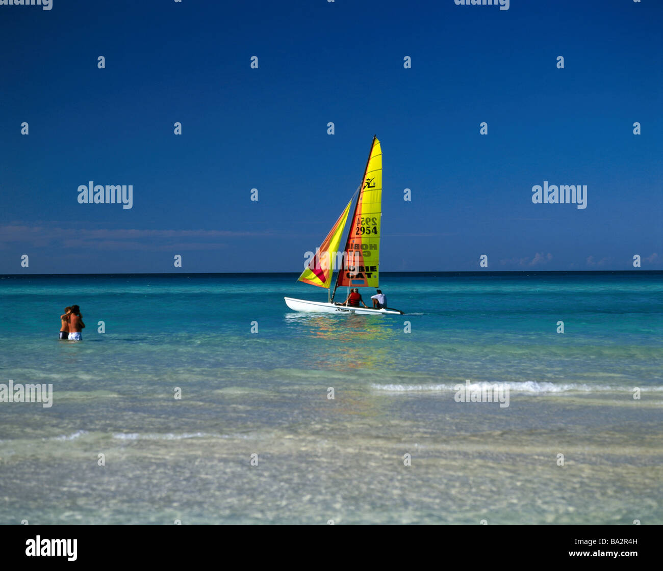 Caribbean sea beach-proximity sailboat swimmers no models release tourists water stands refreshment cooling bath - Stock Image