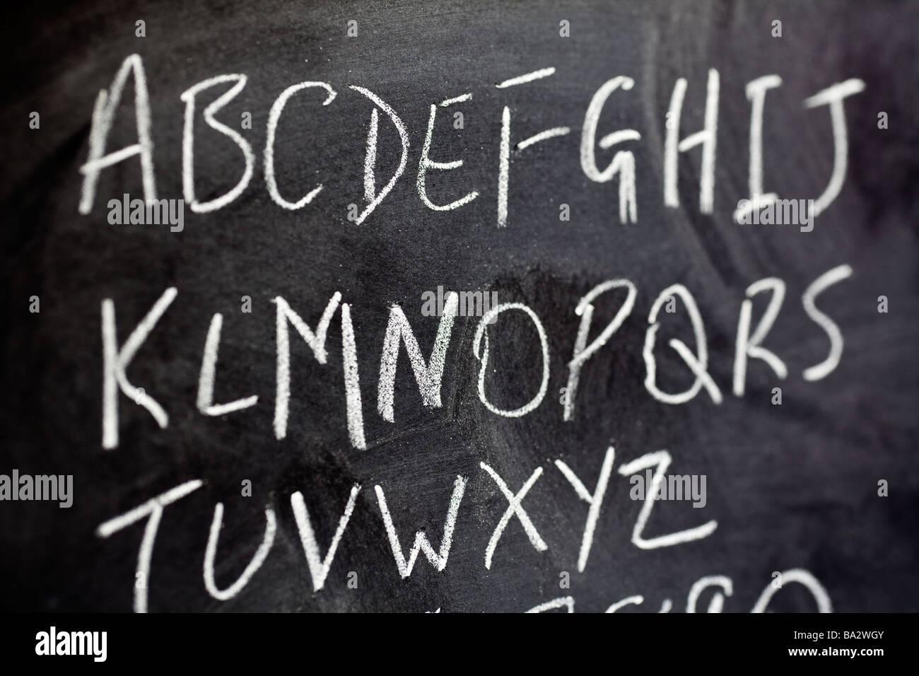 Alphabet written on blackboard close up selective focus - Stock Image