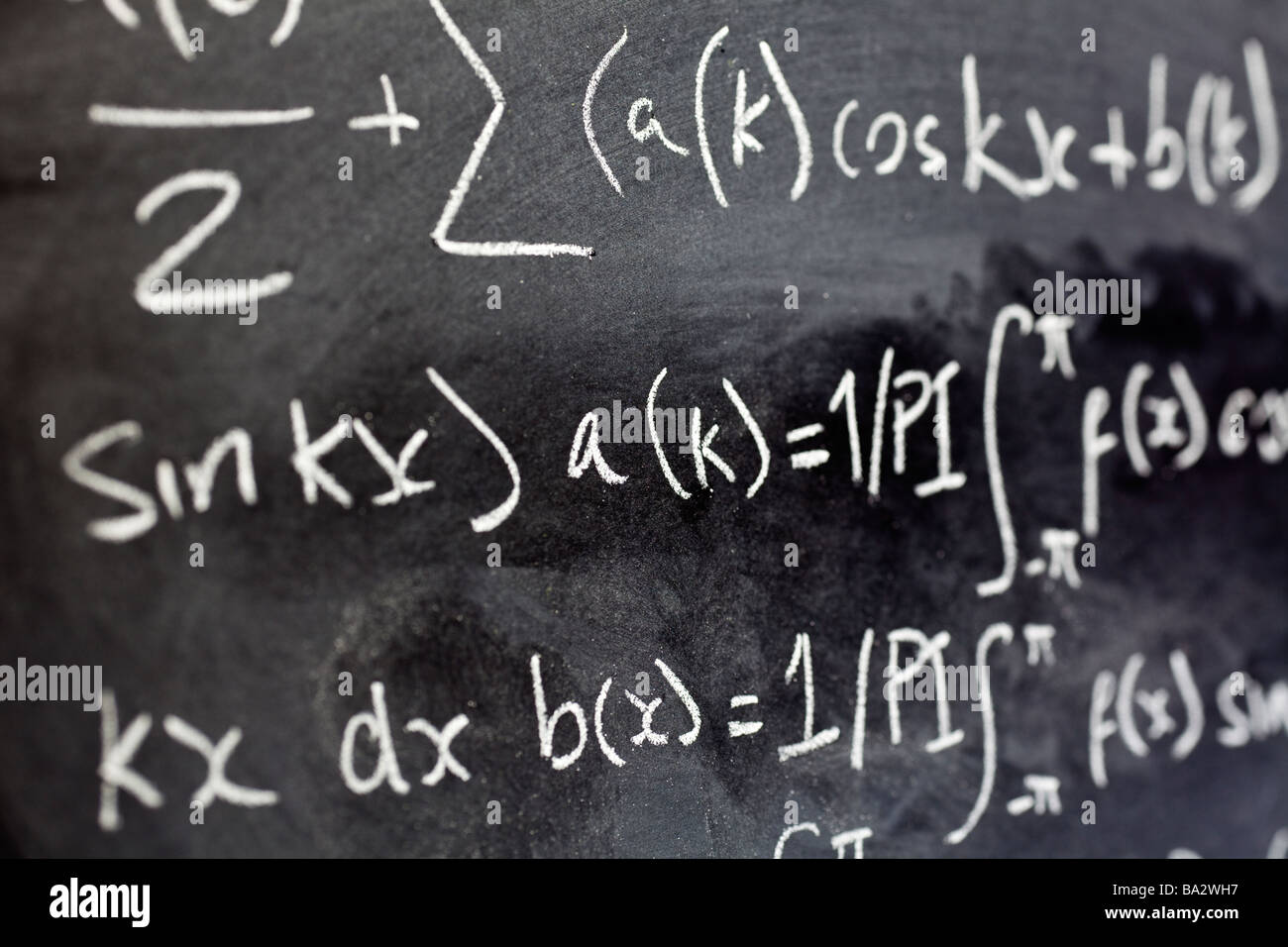 Close up of mathematical equations written on a blackboard in a classroom close up - Stock Image