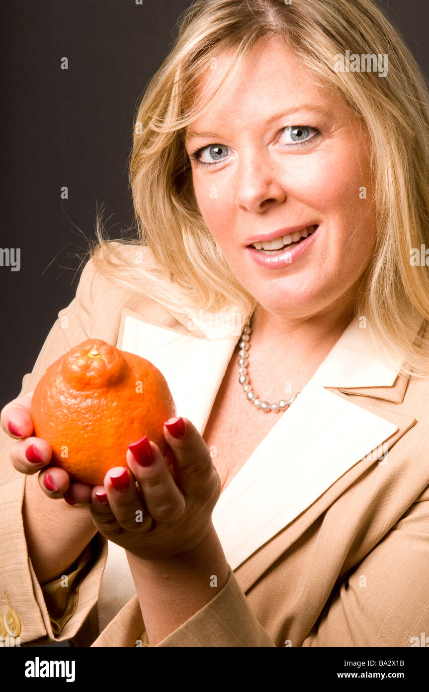 attractive blond woman with mineola orange tangerine fresh fruit for healthy life - Stock Image