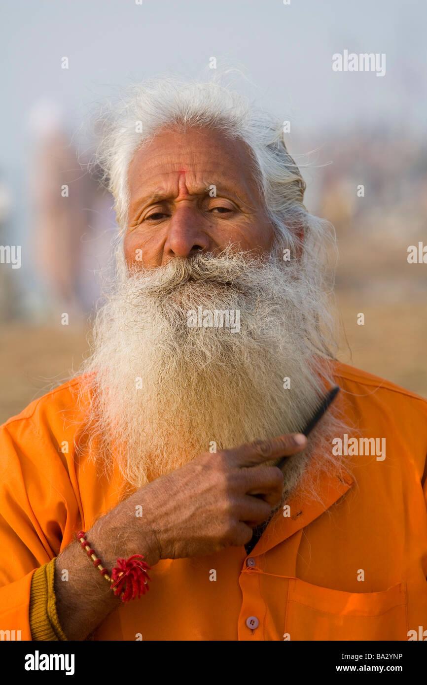 sanyasi ochre ascetic Hindu elder orange old man wise Sadhu grooming white beard Allahabad, India - Stock Image
