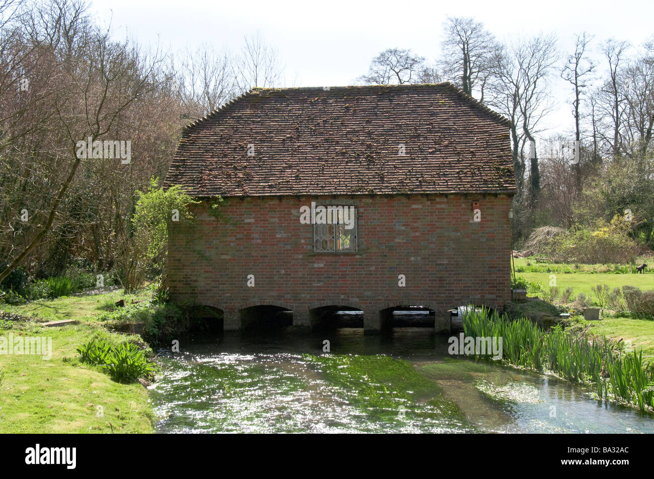 Seventeenth century restored building across a small stream near the village of Warnford in the South Downs National Stock Photo