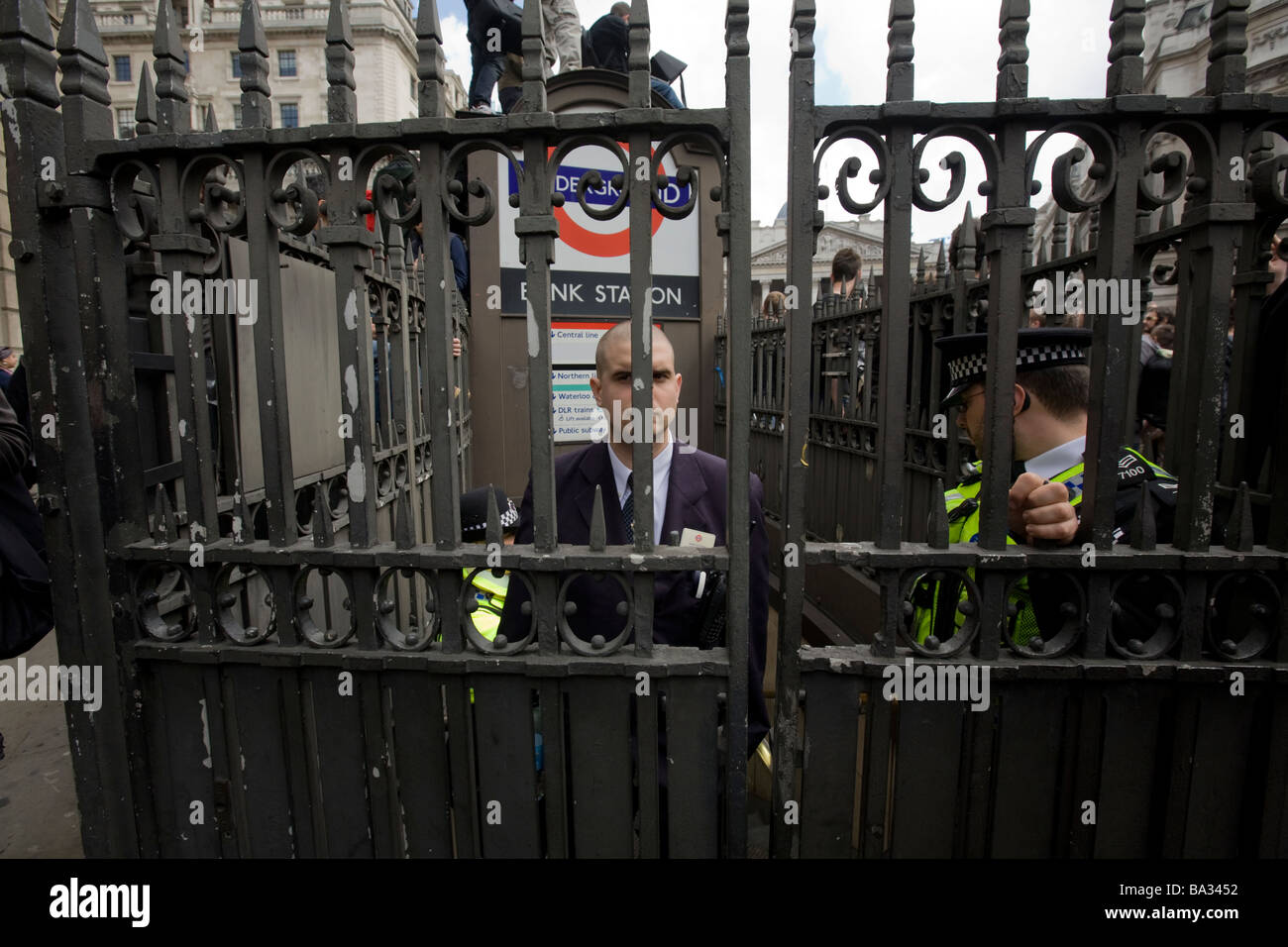 A Transport for London security official watches through the gated entrance to Bank underground station during G20 - Stock Image