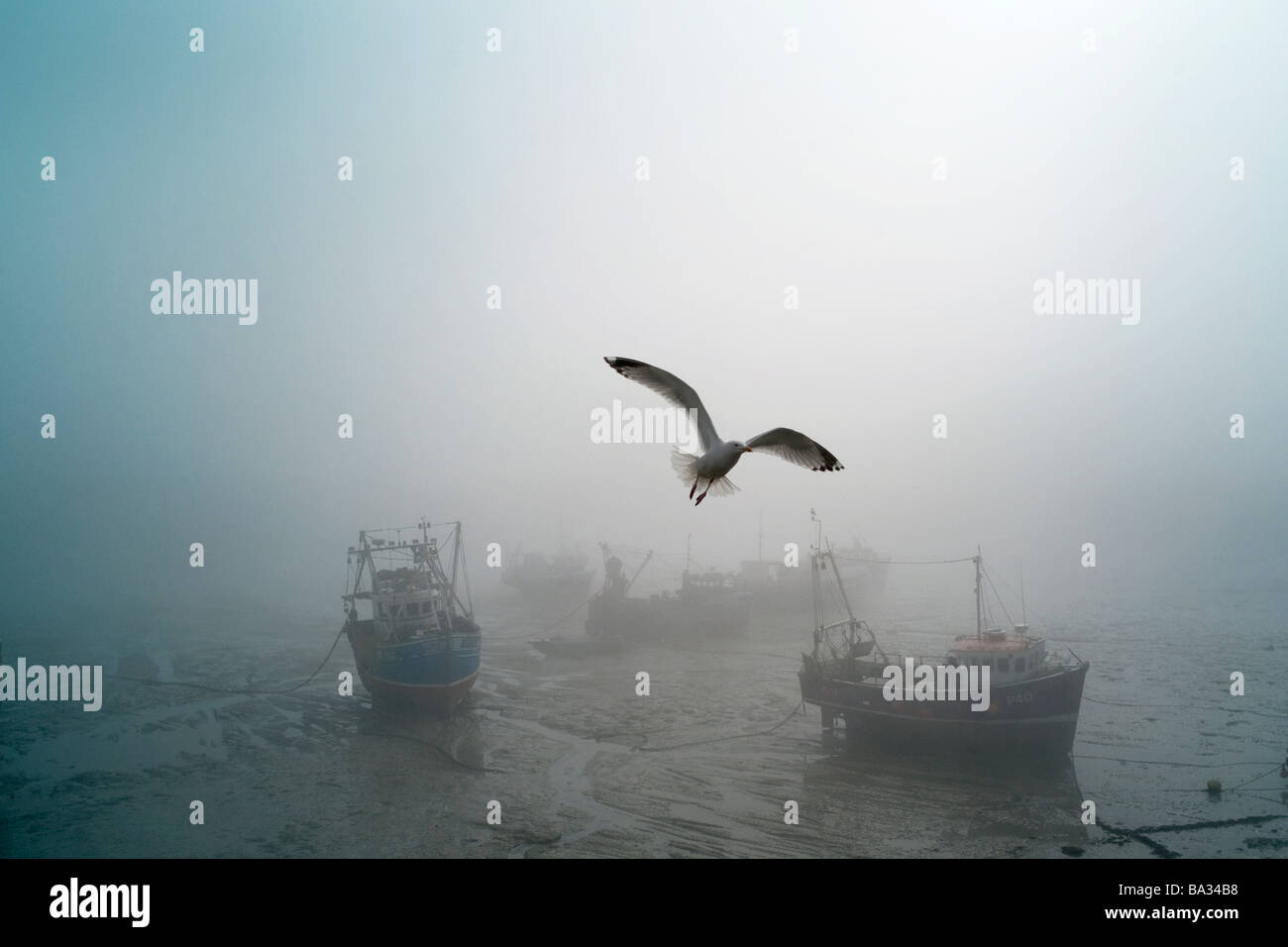 Fishing boats lie aground in sea fog - Stock Image