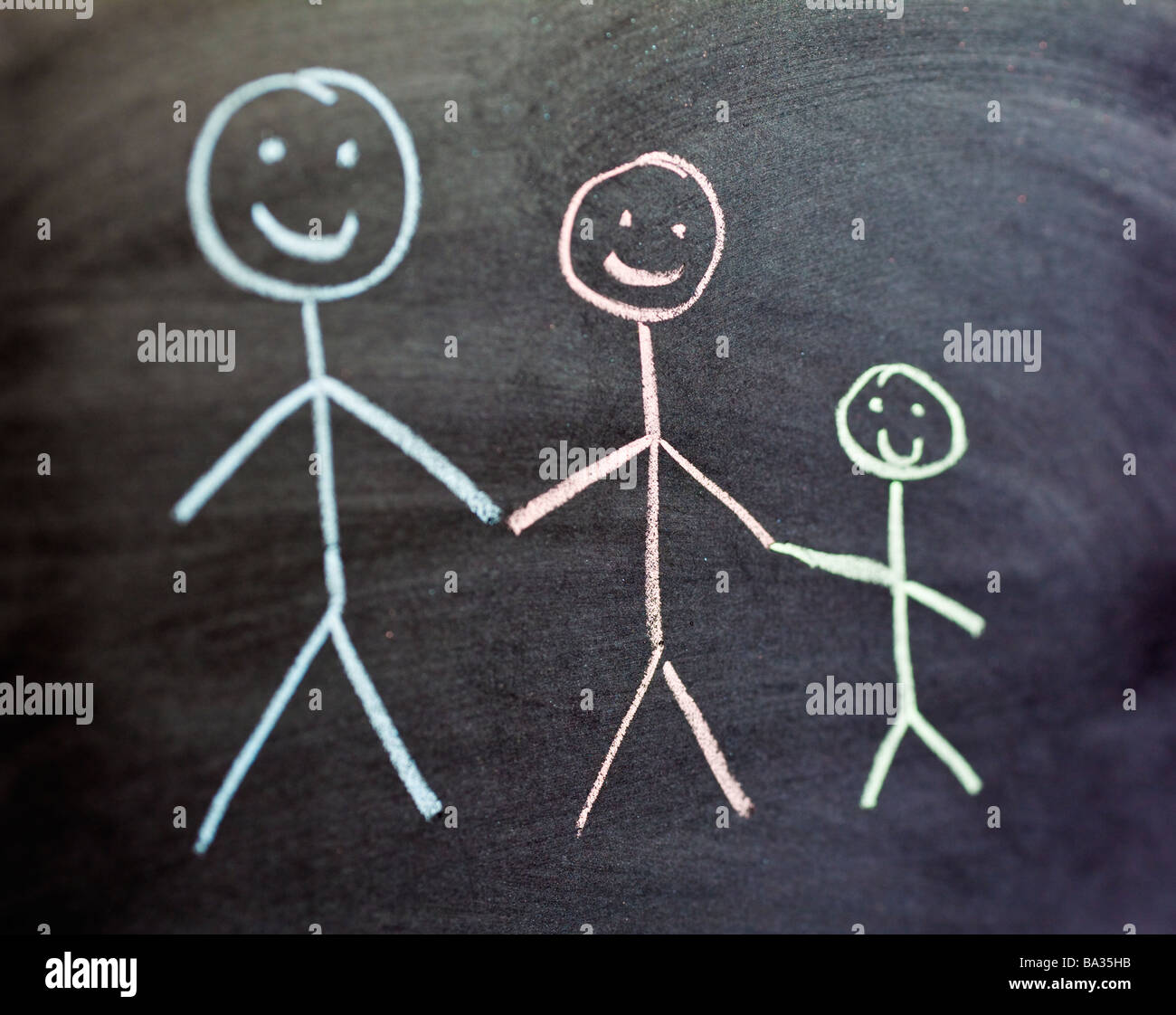 Chalk drawing of two adults and one child family in colour on a blackboard close up selective focus - Stock Image