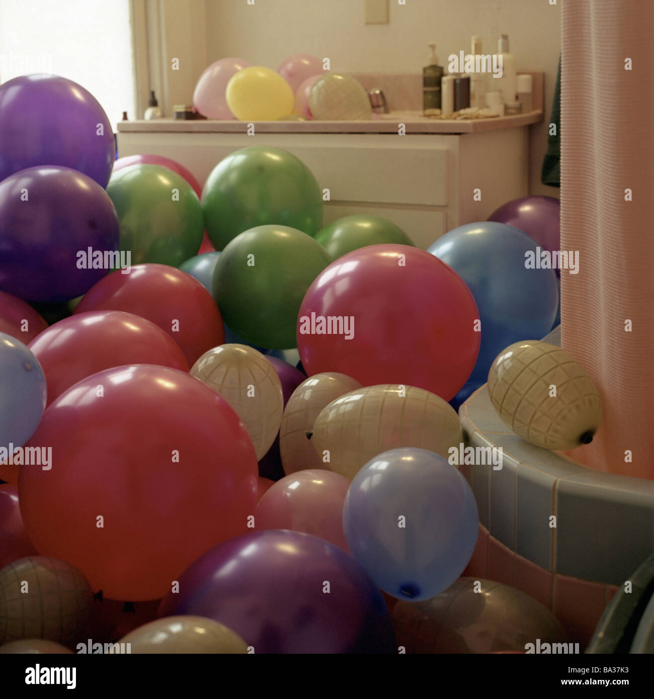Bathroom balloons prank joke humor overfills cleverly surprise wedding wedding-prank bath balloons inflated colorfully - Stock Image