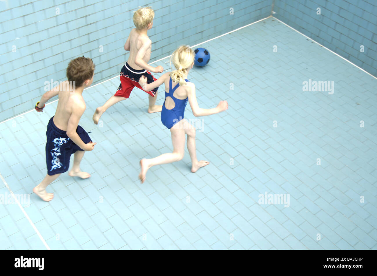 Pool empty children soccer games from above series people girls boys bath-clothing pools basin-ground tiles ball - Stock Image