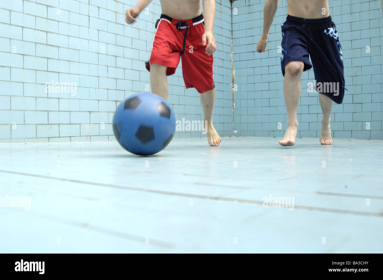 Pool empty children soccer games detail legs series people boys bath-clothing pools basin-ground tiles ball ball - Stock Image